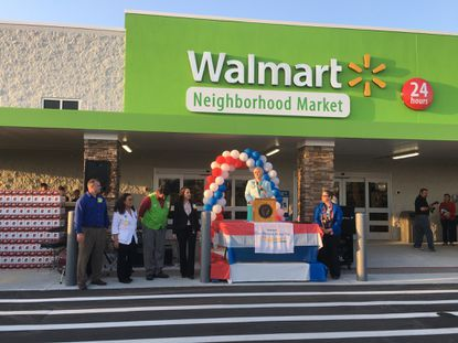 Store Manager Julie Ferreira welcomes shoppers to the Walmart Neighborhood Market in Stevens Plantation at Wednesday's opening.