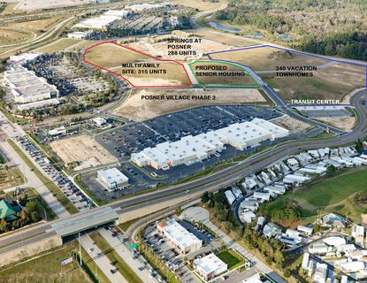This aerial photo shows the first of three new apartment communities, Springs at Posner, under construction. The parcels outlined in red and green are also under contract for multifamily projects. The land outlined in blue is slated for a resort community with 240 vacation townhomes.