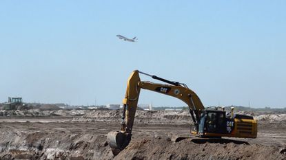 A lone excavator begins work at what will become Orlando International Airport's new south terminal.