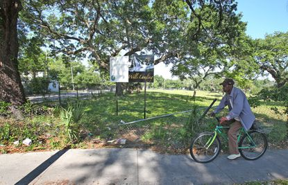 In this photo from April 2014, a bicyclist passes vacant land where a housing development was supposed to be built at Parramore Avenue and Conley Street.