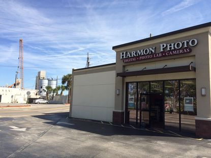 Partial view of the Harmon Photo store and property at the southeast corner of N. Orange Avenue and Virginia Drive, with the new Yard at Ivanhoe development under construction in the background.