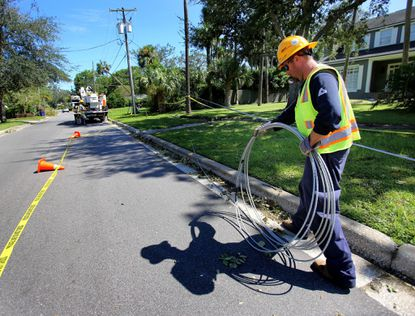 A Duke Energy contractor coils downed power lines on Dommerich Drive during the first stage of assessment and restoration in the aftermath of Hurricane Irma in Maitand, in September 2017. Hurricane Irma's high winds knocked out power to millions across Florida.