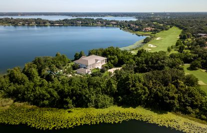 The estate sits on nearly six acres with panoramic views of Lake Bessie.