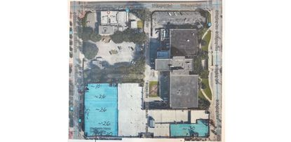 Bordered by W. Central Boulevard, S. Hughey Avenue and W. Church Street, this 8.4-acre block planned for the Orlando Magic's Sports Entertainment Complex is shown here pre-demolition. Two areas highlighted in blue, now vacant land, will be used for temporary parking in front of Amway Center.