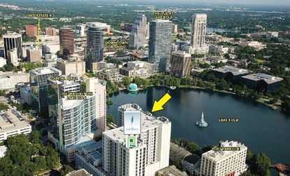 An aerial photo of the 16-story The Paramount on Lake Eola condo building, showing its place south of Lake Eola in context with the rest of Downtown Orlando.