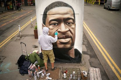 Graffiti artist Akse spray paints a mural of George Floyd in Manchester's northern quarter onJune 3 in Manchester, United Kingdom. The death of an African-American man, George Floyd, while in the custody of Minneapolis police has sparked protests across the United States, as well as demonstrations of solidarity in many countries around the world.