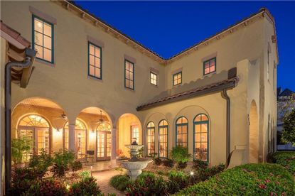 The courtyard entrance to this six-bedroom esate home on Celebration's Eastlawn Drive creates a sense privacy and celebrates the arches and columns found throughout the home.