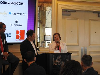 "Catherine Reeves of Highwoods Properties receiving a ""Lifetime Achievement Award"" on May 31 from NAIOP Central Florida. Chapter president Joe Rossi stands to the left at podium."