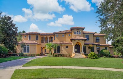 The entrance of the six-bedroom home features an arched courtyard entry into a four-car garage, multiple second-story decks and a pool and spa area.