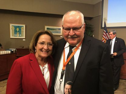 John Smogor, wearing a necktie depicting Ronald Reagan, is retiring from his post as Orange County Development Review Committee Chair and Planning Administrator. He's shown with Orange County Mayor Teresa Jacobs.